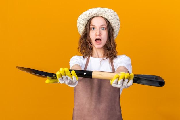 Sorpreso giovane giardiniere femminile che indossa guanti da giardinaggio che tengono fuori la vanga isolata sulla parete arancione