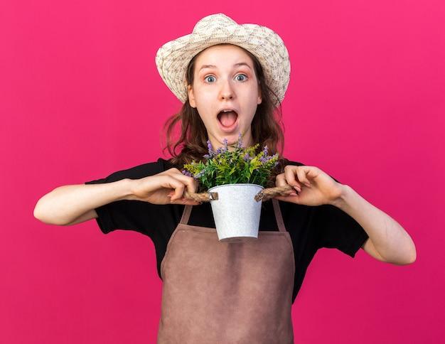 植木鉢に花を持ってガーデニング帽子をかぶって驚いた若い女性の庭師