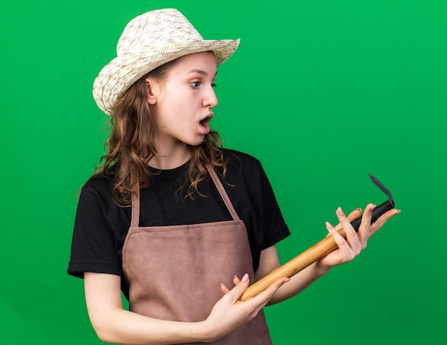Surprised young female gardener wearing gardening hat holding and looking at rake isolated on green wall