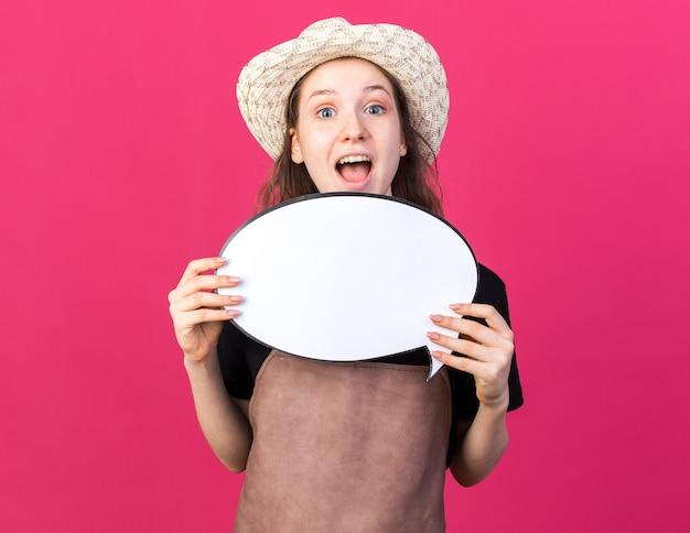 吹き出しを保持しているガーデニングの帽子をかぶって驚いた若い女性の庭師