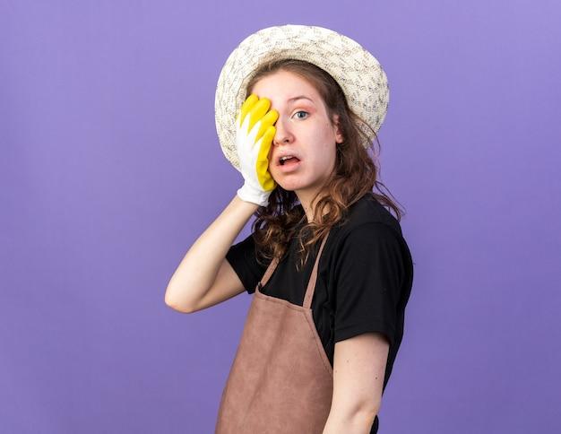 Sorpreso giovane giardiniere femminile che indossa un cappello da giardinaggio con guanti ha coperto il viso con la mano isolata sulla parete blu