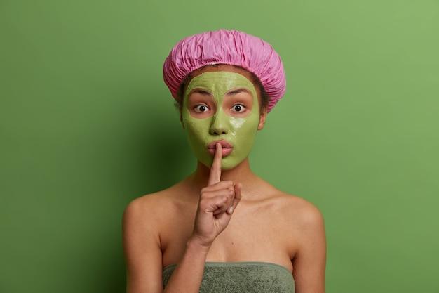 그녀의 얼굴에 녹색 껍질을 벗기고 놀란 젊은 여성 모델은 침묵 제스처를 만들고 미용사의 비밀을 말하고 샤워 캡을 쓰고 생생한 벽에 포즈를 취합니다. 아름다움과 얼굴 관리 개념