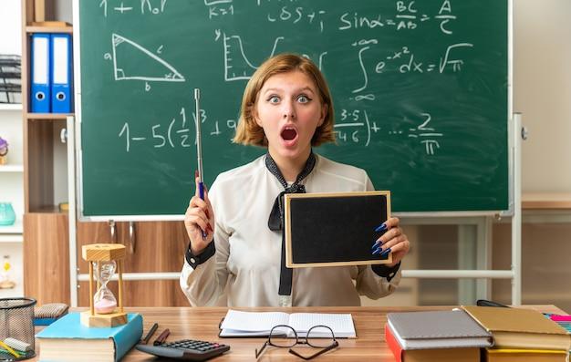 Удивленная молодая учительница сидит за столом со школьными принадлежностями, держа мини-доску с указателем в классе
