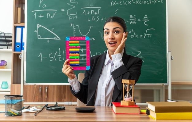 Surprised young female teacher sits at table with school supplies holding abacus putting hand on cheek in classroom