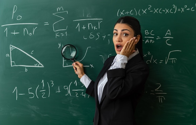 Sorpreso giovane insegnante femminile in piedi davanti alla lavagna mettendo la mano sulla guancia in classe