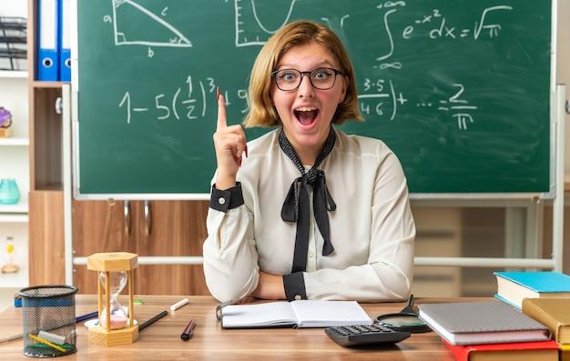 Sorpreso giovane insegnante di sesso femminile con gli occhiali si siede al tavolo con gli strumenti della scuola puntati su in classe