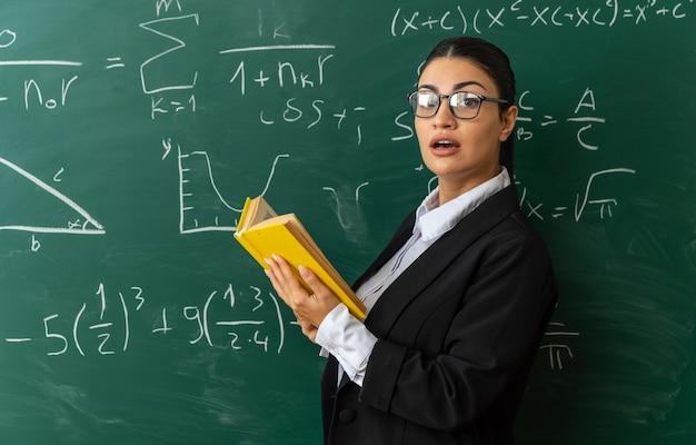 Sorpreso giovane insegnante di sesso femminile con gli occhiali in piedi davanti alla lavagna con in mano un libro in aula