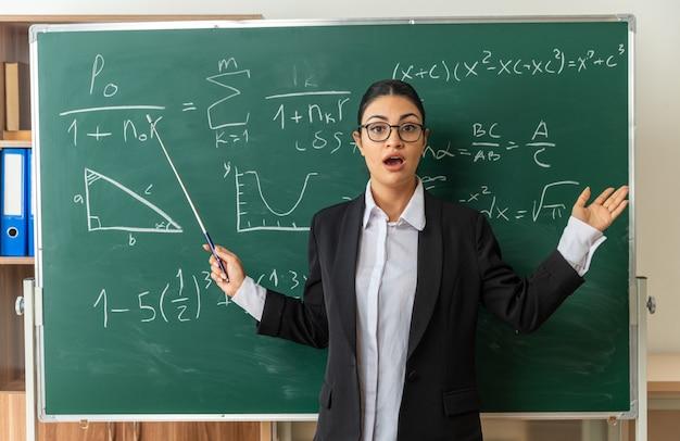 Sorpreso giovane insegnante di sesso femminile con gli occhiali in piedi di fronte alla lavagna tenendo il puntatore stick allargando le mani in classe