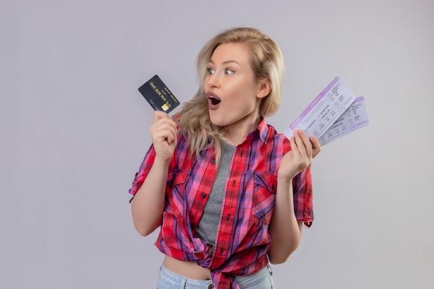 Giovane viaggiatore femminile sorpreso che indossa la camicia rossa che tiene carta di credito e biglietti sulla parete bianca isolata