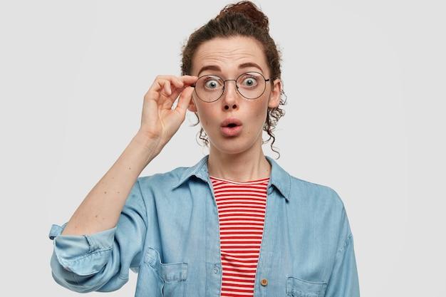 Sorpresa giovane femmina con la faccia lentigginosa, guarda con shock, indossa gli occhiali, è stupita, vestita con un maglione rosso a righe e una camicia di jeans, ha assistito a un incidente scioccante. concetto di stupore