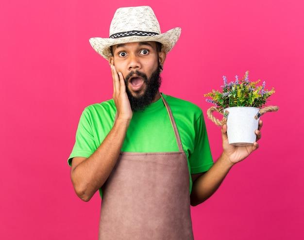 Sorpreso giovane giardiniere afro-americano che indossa cappello da giardinaggio tenendo il fiore in vaso di fiori mettendo la mano sulla guancia isolata sul muro rosa