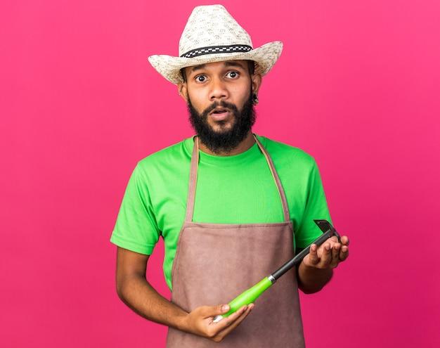 분홍색 벽에 고립 된 괭이 갈퀴를 들고 정원 모자를 쓰고 놀란 젊은 정원사 아프리카계 미국인 남자