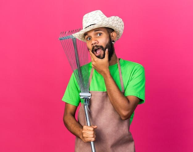Sorpreso giovane giardiniere afro-americano che indossa cappello da giardinaggio tenendo il rastrello delle foglie afferrò il mento isolato sulla parete rosa
