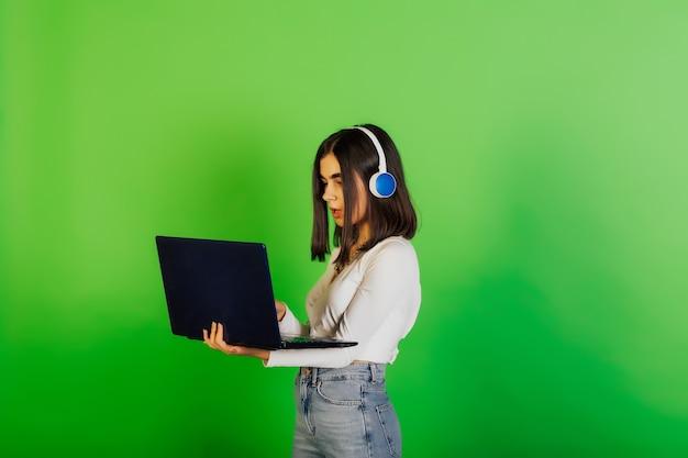 緑のスタジオの表面に隔離されたラップトップコンピューターを保持している驚いた若い女の子、大学生または大学生。