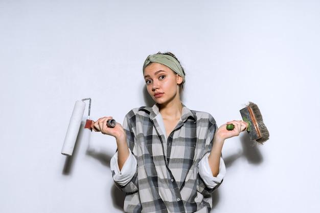 Удивленная молодая девушка делает ремонт в своей новой квартире, держит кисть и валик для покраски стен и не может выбрать