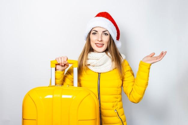 黄色のジャケットとサンタクロースの帽子に身を包んだ驚いた若い女の子は黄色のスーツケースを保持し、彼の手のひらを持ち上げます