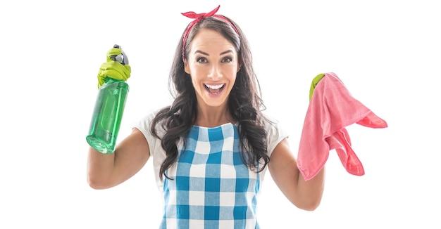 緑の洗剤とピンクのクリーニングシートを持ったハウスキーイングの服を着た驚いた少女。