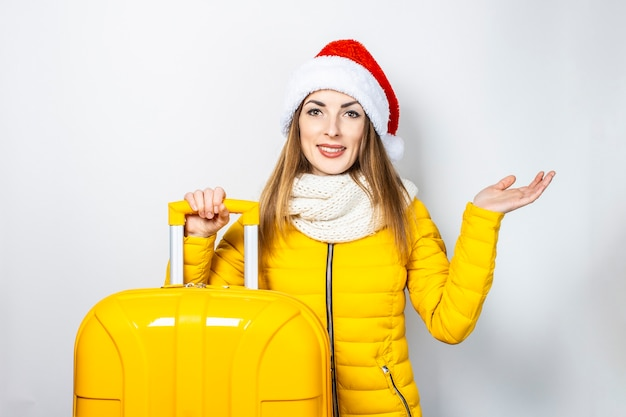 Surprised young girl dressed in a yellow jacket and santa claus hat, holds a yellow suitcase and holds his hand palm up
