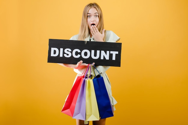 Surprised young girl has discount sign with colorful shopping bags isolated over yellow