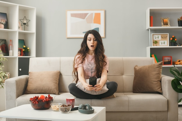 Удивленная молодая девушка держит и смотрит на телефон, сидя на диване за журнальным столиком в гостиной