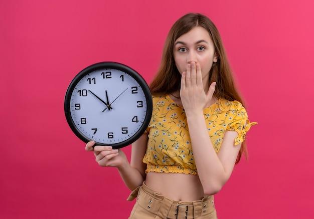 Ragazza giovane sorpresa che tiene orologio e mettendo la mano sulla bocca sulla parete rosa isolata