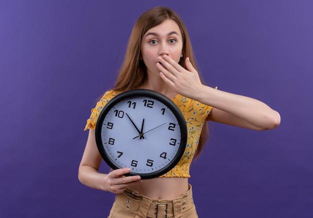 Ragazza giovane sorpresa che tiene orologio e mettendo la mano sulla bocca sulla parete viola isolata
