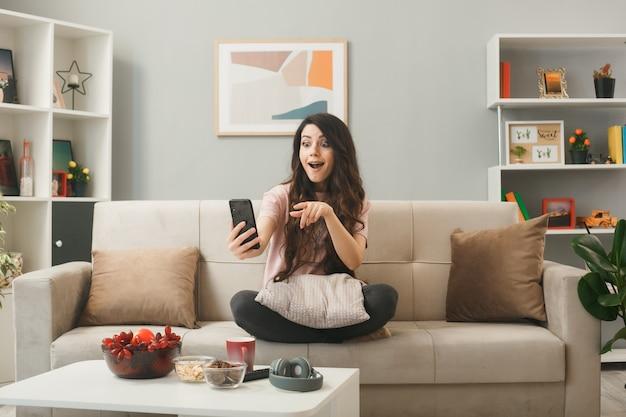 Ragazza sorpresa che tiene in mano e indica il telefono seduto sul divano dietro il tavolino da caffè nel soggiorno