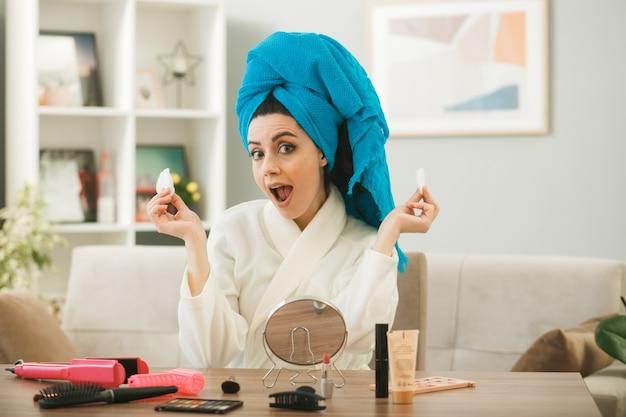 Удивленная молодая девушка, держащая губку, сидит за столом с инструментами для макияжа в гостиной