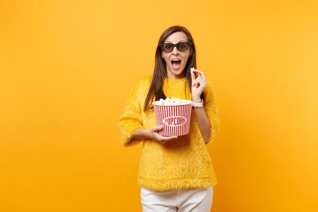 3d 아이맥스 안경을 쓴 어린 소녀가 영화를 보고 밝은 노란색 배경에 격리된 팝콘 양동이를 들고 놀랐습니다. 영화, 라이프 스타일 개념에서 사람들은 진실한 감정. 광고 영역입니다.