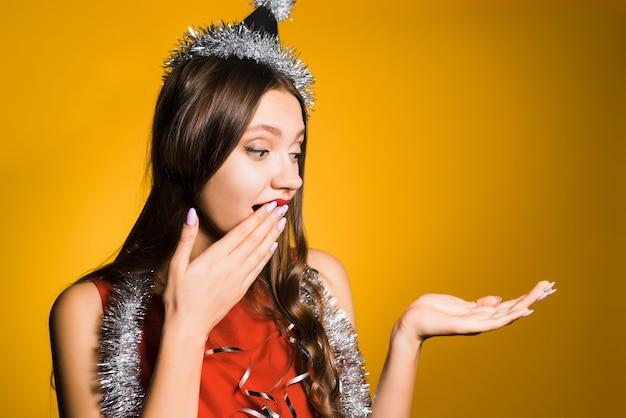 Удивленная молодая девушка в красном платье и с серебряной мишурой на шее показывает руку на чем-то