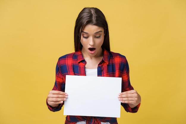 黄色の背景で隔離の手に白いプラカード紙と赤いシャツを着て驚いた若い女の子。