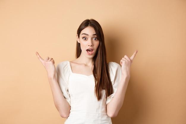 驚いた少女は、左右を横向きに、あえぎながら驚いたと言って、ベージュの背景の2つのクールな選択肢を示しました。