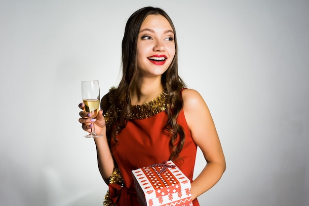 A surprised young girl in a red dress and with a gold tinsel around her neck celebrating the new year 2018, holding a glass of champagne