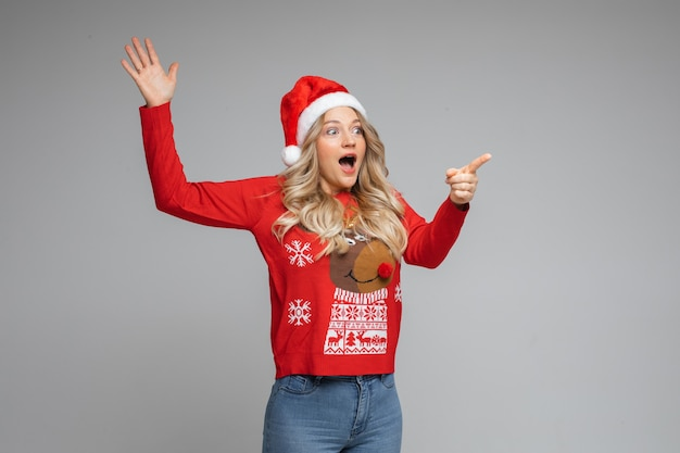 Surprised young girl in santa hat and red warm winter sweater point aside by finger on gray background with copy space