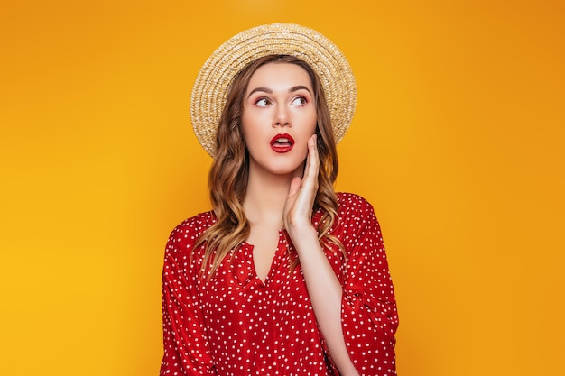 Surprised young girl in a straw hat in a red dress with a red lipstick looks away at  portrait of a shocked young woman in summer clothes on an orange wall sale concept