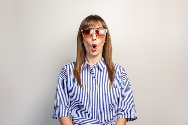 Surprised young girl in sunglasses on a light background