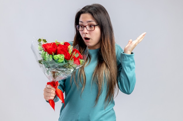 Surprised young girl on valentines day holding and looking at bouquet spreading hand isolated on white background