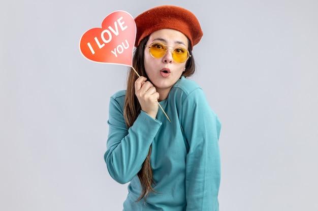 Ragazza sorpresa il giorno di san valentino che indossa un cappello con gli occhiali che tengono cuore rosso su un bastone con ti amo testo isolato su sfondo bianco