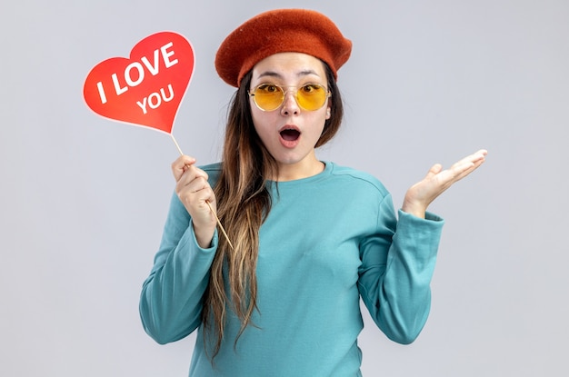 Surprised young girl on valentines day wearing hat with glasses holding red heart on a stick with i love you text spreading hand isolated on white background