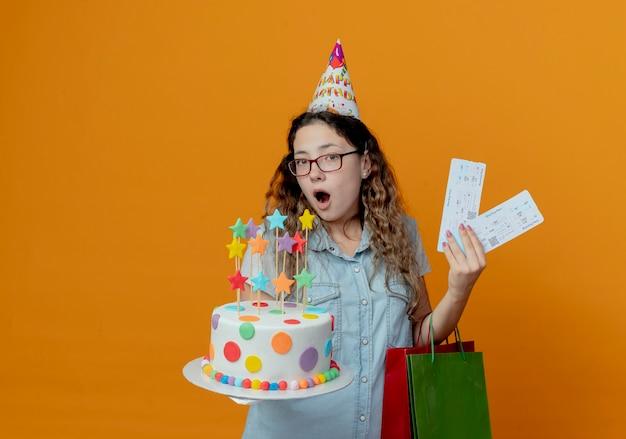 オレンジ色の背景で隔離の誕生日ケーキとギフトバッグとチケットを保持している眼鏡と誕生日キャップを身に着けている驚いた若い女の子