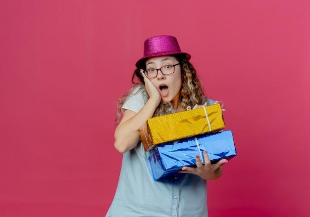 Удивленная молодая девушка в очках и розовой шляпе держит подарочные коробки и кладет руку на щеку, изолированную от розового