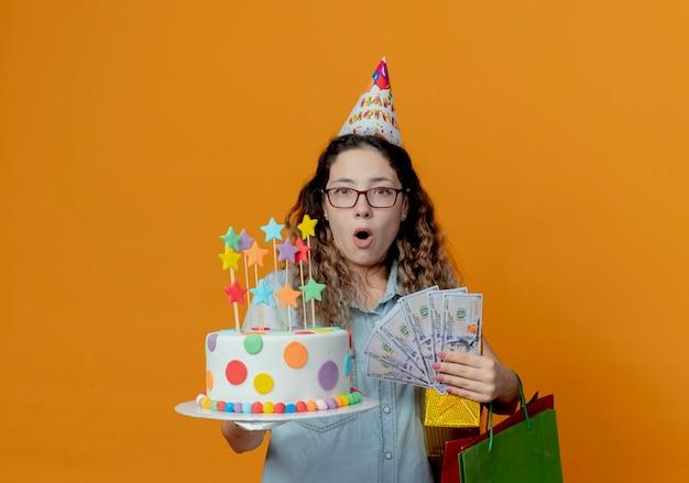 Ragazza giovane sorpresa con gli occhiali e berretto di compleanno che tiene la torta di compleanno con scatole regalo con borse e soldi sull'arancia
