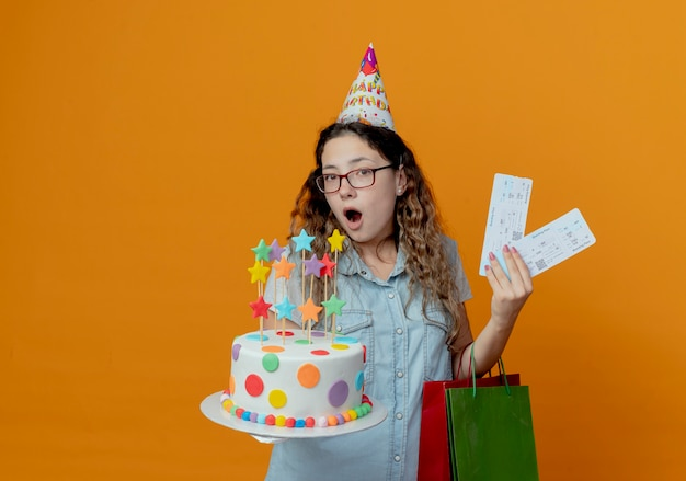 Surprised young girl wearing glasses and birthday cap holding tickets with birthday cake and gift bags isolated on orange background
