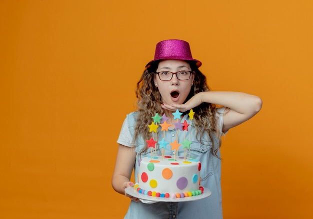 Ragazza giovane sorpresa con gli occhiali e cappello rosa tenendo la torta di compleanno e mettendo la mano sotto il mento isolato su sfondo arancione