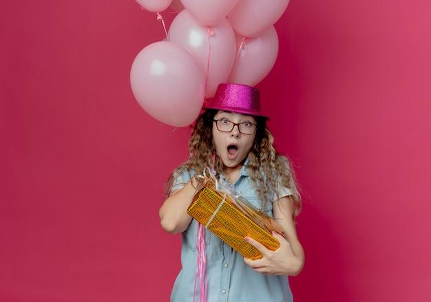 Ragazza giovane sorpresa con gli occhiali e cappello rosa che tiene il contenitore di regalo con palloncini isolati in rosa
