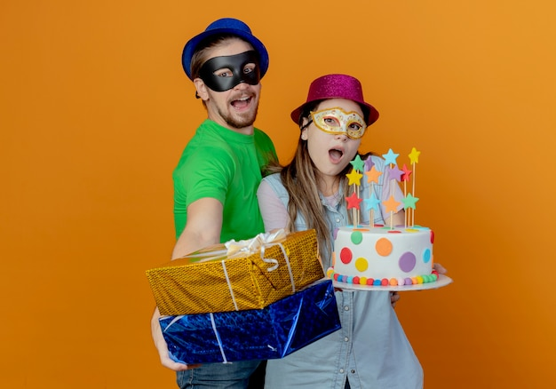 Surprised young girl wearing pink hat and masquerade eye mask holds birthday cake and joyful handsome man in blue hat wearing masquerade eye mask holding gift boxes isolated