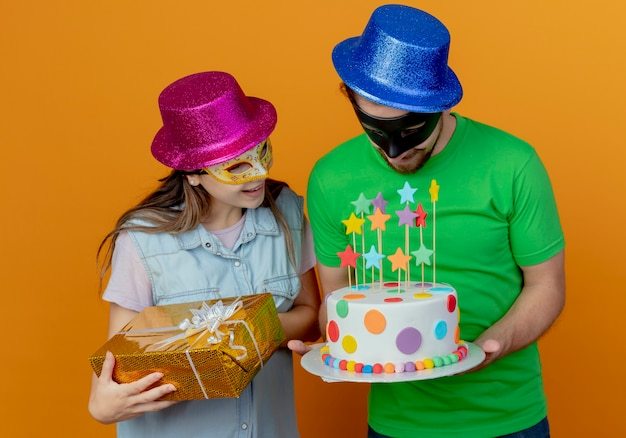 Surprised young girl wearing pink hat and masquerade eye mask holds gift box and looks at birthday cake holding by pleased handsome man in blue hat wearing masquerade eye mask