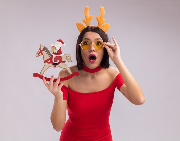 Surprised young girl wearing reindeer antlers headband and glasses holding santa on rocking horse figurine looking at camera grabbing glasses isolated on white background