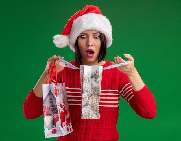Удивленная молодая девушка в шляпе санта-клауса держит рождественские подарочные пакеты, открывая один, глядя внутрь него, изолированного на зеленой стене