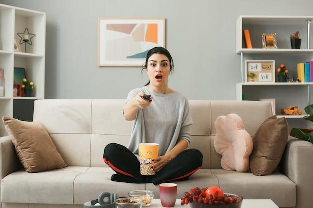 Ragazza sorpresa con secchio di popcorn che tiene il telecomando della tv, seduta sul divano dietro il tavolino da caffè nel soggiorno